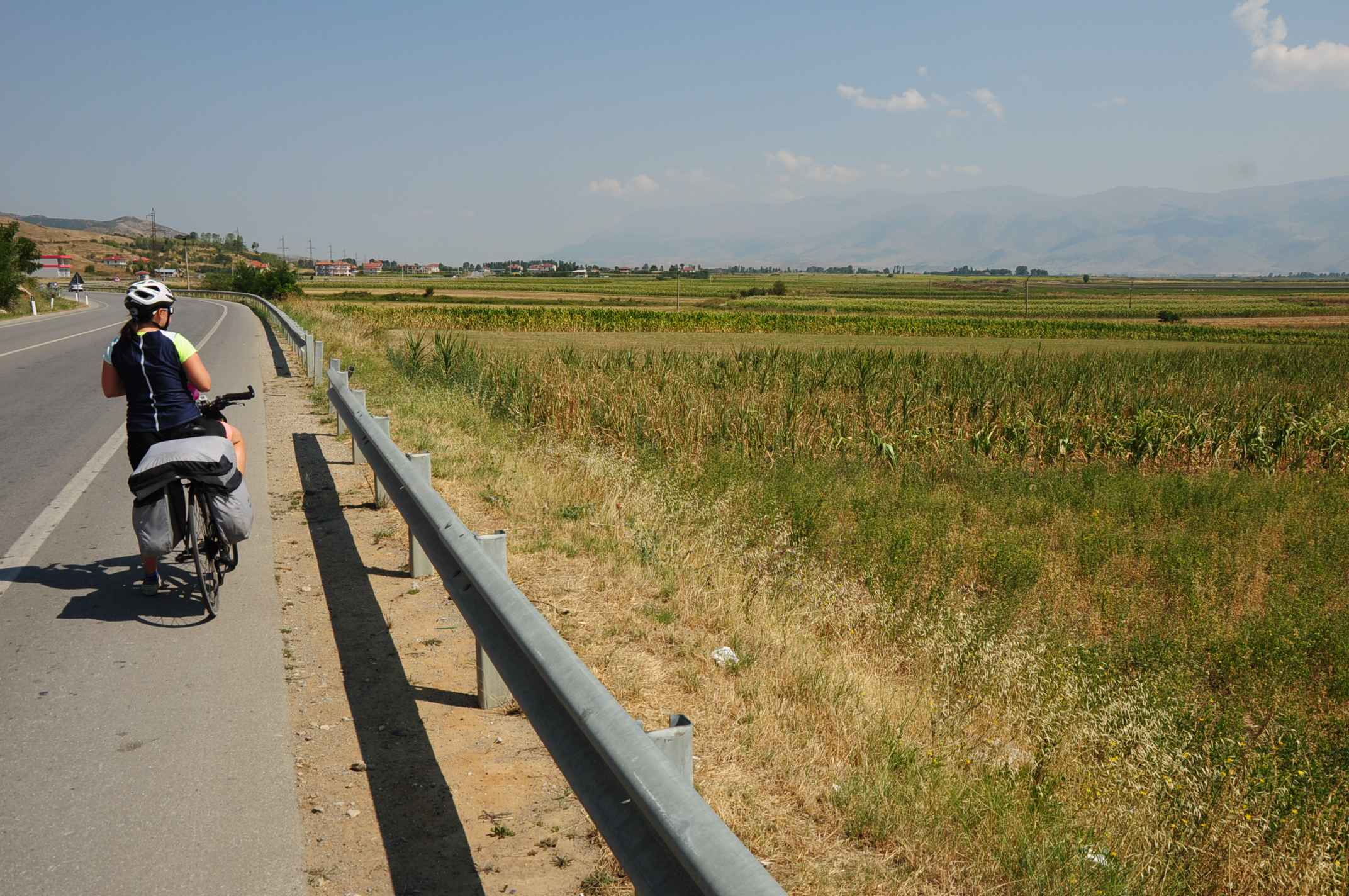 Straight road and agricultural land between Korçë and Pogradec