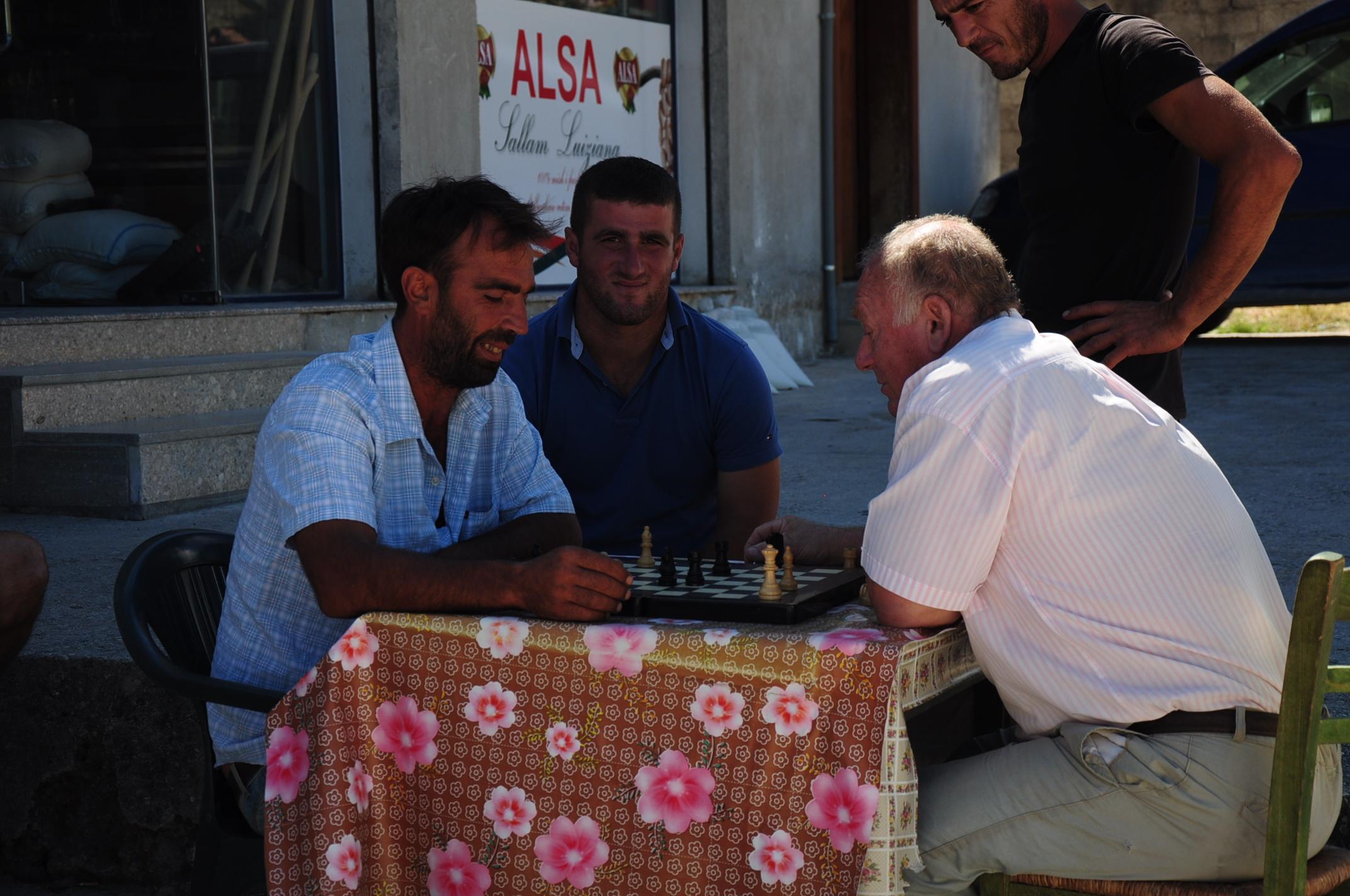 Sakkozó férfiak egy falusi bár előtt