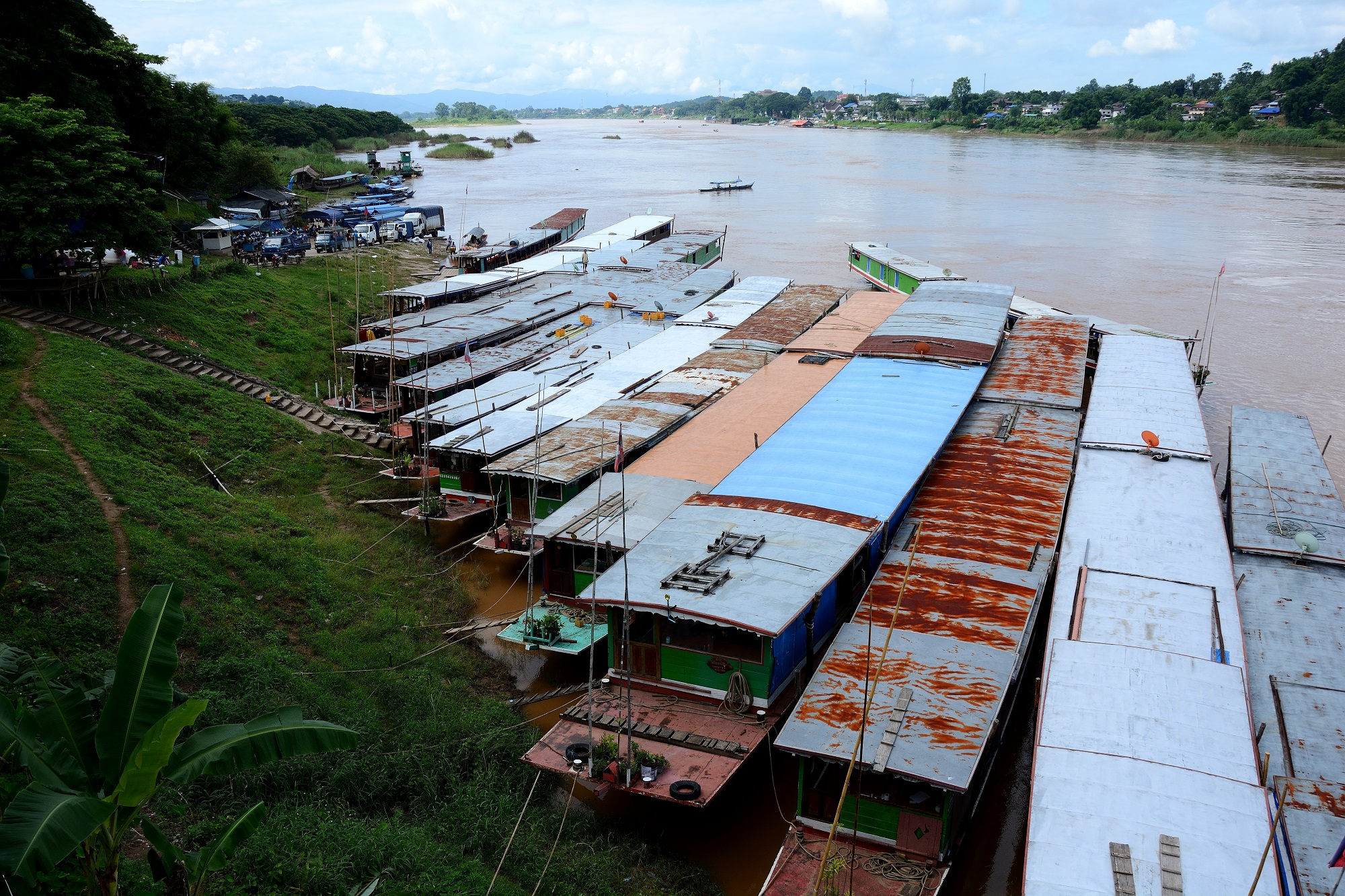 A row of long boats waiting at the pier in Huay Xai, Laos