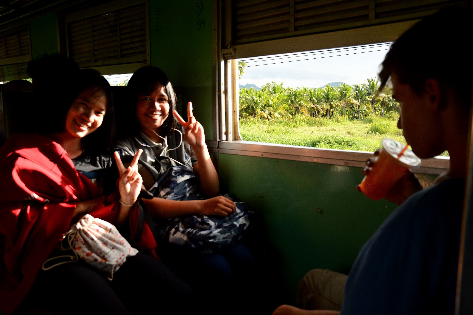 Thai girls on board the train heading south